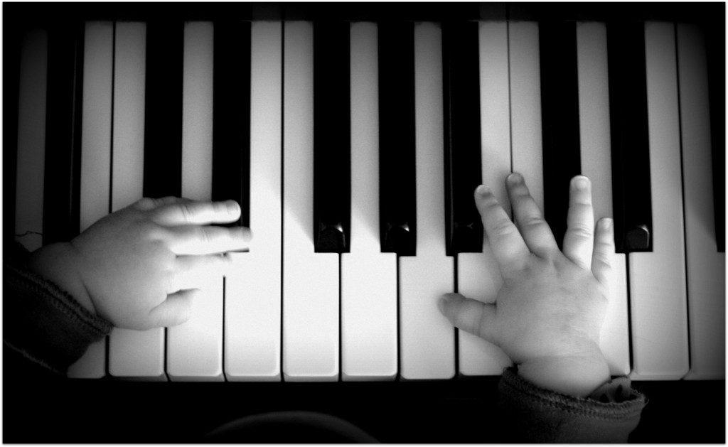 Kinderfinger auf dem Klavier von oben